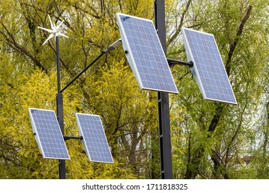 Street electricity by small windmill and solapanels in the city against buildings in daytime. Concept of newable, eco or environmentally friendly and clean energy.