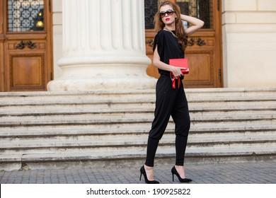 Street fashion. Beautiful young woman wearing backless jumpsuit. Urban fashion.