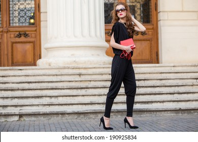 Street fashion. Beautiful young woman wearing backless jumpsuit. Urban fashion.
