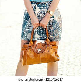 Street fashion and beauty concept. Stylish lady holding luxury natural leather handbag in hands. Closeup of modern trendy bag in female hands. Woman in smart and chick clothing.