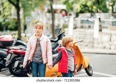Street fashion for children. Boy and girl wearing padded jackets. Little brother and sister spending time together