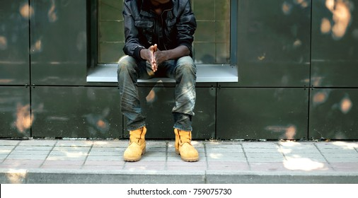 Street fashion concept, african man in black jacket, jeans and boots sitting in the city