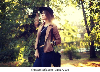 Street fashion concept - closeup portrait of a pretty girl. Wearing hat and suede jacket  holding bag with fringe. Beautiful autumn woman. Artsy bohemian style. Outside, fall fashion