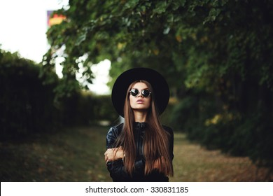 Street fashion concept - closeup portrait of a pretty girl. Wearing hat and leather jacket, round sunglasses. Autumn woman. Artsy bohemian rock style. Fall fashion. Toned style instagram filters