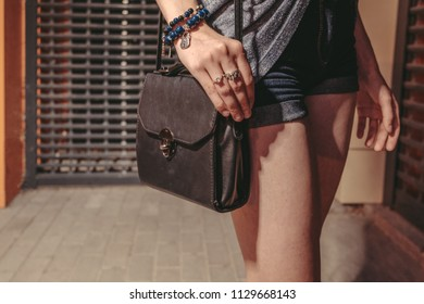 Street Fashion Concept. Fashionable small black handbag with arm on its top, hipster girl posing near the night club door closed with metal grid on a warm summer night in denim shorts, image with