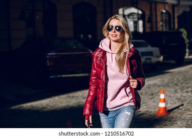 Street fashion concept - portrait of a beautiful girl sitting outside, blue jeans, sunglasses, hard lights, red jacket, autumn weather