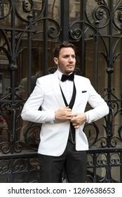 Street fashion concept. Portrait of elegant young handsome man. Paris buildings as background.