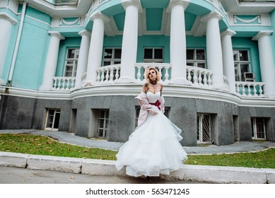 Street fashion concept: portrait of young beautiful woman wearing wedding white dress and pink coat in the city. Red hair girl outdoor. Old architecture background. Amazing tattoo bride. Color.