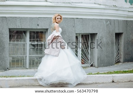 0b82c622492b Street fashion concept: portrait of young beautiful woman wearing wedding  white dress and pink coat