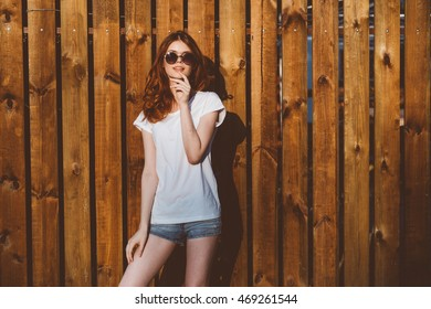 Street fashion concept - pretty young slim woman in tank top and shorts , sunglasses posing on the background of wooden wall