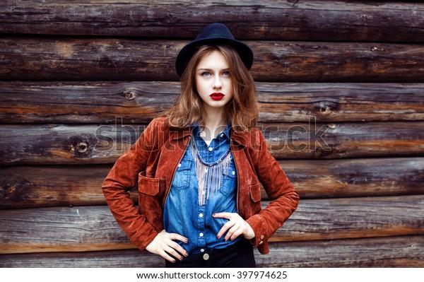 ストリートファッションのコンセプト。カジュアルなスエードの上着を着た若い女性のビンテージポートレート。ヒップスターのスタイル。