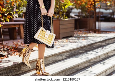 Street fashion details: elegant woman wearing polka dot midi skirt, golden wrist watch, mirror shine ankle boots, heels, holding white leather bag with yellow tweed part. Copy, empty space for text