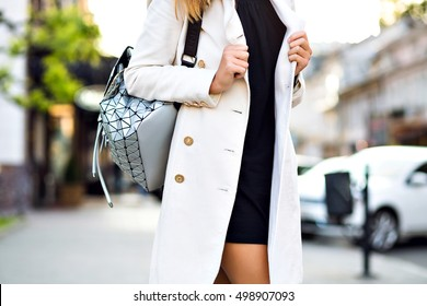 Street fashion details, woman posing at Europe city center , autumn spring time, stylish cashmere coat, sexy dress, unusual backpack, soft colors.