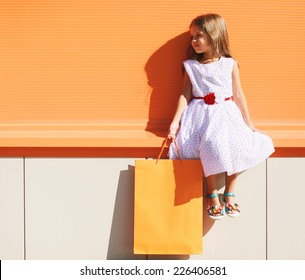 Street fashion kid, pretty little girl in dress with shopping bag near colorful wall outdoors