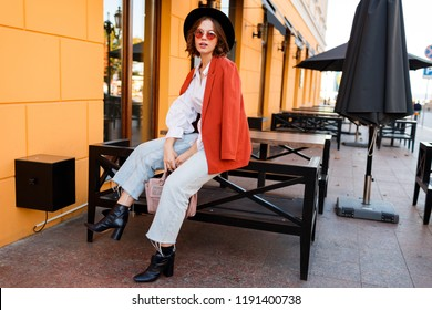 Street fashion look.  Amazing stylish traveling  girl in  trendy autumn outfit  posing outdoor . Cafe with yellow walls on background.  Model wearing orange jacket and black hat.
