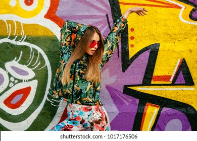 Street fashion look of attractive young woman in red sunglasses, dressed in colorful jacket with hood, leggings, posing near the wall with graffiti.