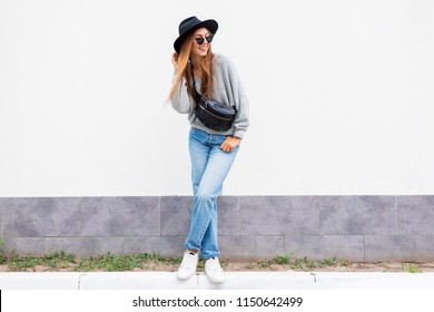 Street fashion look, autumn outfit.  Full length image of Pretty brunette model in black hat posing on white background.