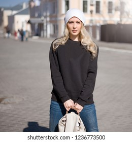 Street fashion look. Beautiful girl wearing white hat, black hoody, jeans and beige backpack in the city