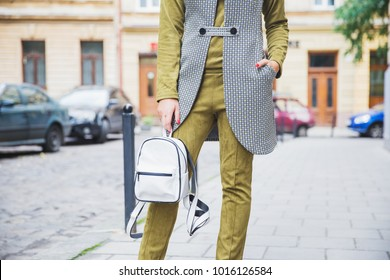 Street fashion look, stylish spring outfit. Woman in velvet olive costume with white backpack on the street. Spring fashion trends