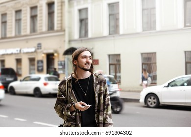 Street fashion, modern lifestyle, technology and communication. Outdoor shot of attractive fashionable guy with beard using 3G internet on mobile phone, standing alone in urban surroundings