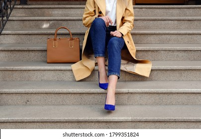 Street fashion outfit, model in blue jeans coat and big leather brown handbag in high heel shoes sitting on the beige stair, outdoor