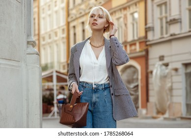 Street fashion photo of elegant  woman wearing trendy white blouse, stylish checkered blazer, high waist jeans, holding brown faux croco leather textured bag. Model walking in street of European city