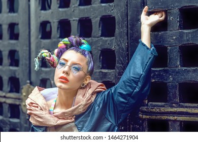 Street fashion portrait of funky girl model with colorful braided crazy hair and urban outfit – Avant garde style of unique hipster woman with piercing and cool eyeglasses – futuristic teen style