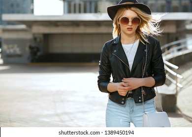 Street fashion portrait of a glamor blonde woman wearing hat and vintage sunglasses. Empty space