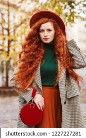 Street fashion portrait of young beautiful redhead woman with freckles, very long curly hair, wearing houndstooth coat, green turtleneck, orange hat, pleated skirt, holding stylish red round handbag