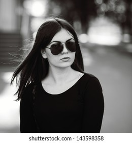 street fashion portrait of a young dark hair girl in black and white