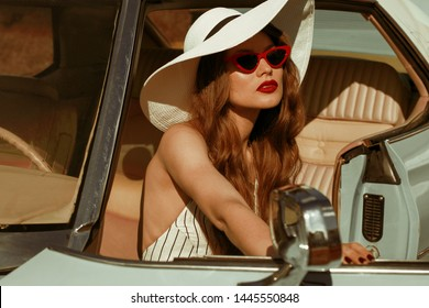 Street fashion portrait of young elegant luxury lady wearing white sunglasses, wide brim hat, striped linen jumpsuit, posing in the retro car. Copy, empty space for text