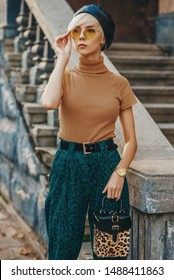 Street fashion portrait of young elegant woman wearing leather beret, beige glasses, turtleneck, green corduroy high waist trousers, golden wrist watch, holding trendy leopard printed box bag