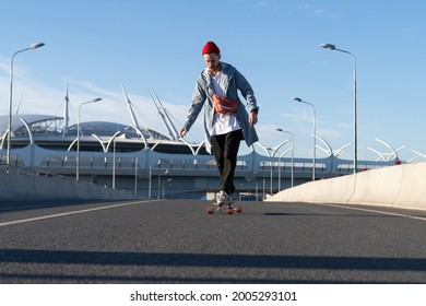 Street fashion and urban lifestyle: hipster man dressed in trendy casual clothes longboarding on city road at sunset wear stylish waist bag and red hat. Young guy on longboard skating alone on bridge