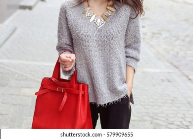 Street fashion woman look. Fashionista model in the city. Stylish pretty fashionable young brunette woman in gray sweater with red leather bag walking on the street.