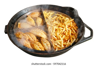 Street fast food- French fries and fried beef and chicken pies on a big frying pan. Isolated on white