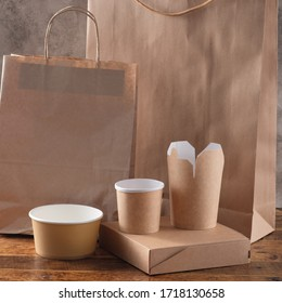 Street fast food paper cups, plates and containers. Eco-friendly food packaging on wooden background. Copy space. Carering of nature and recycling concept.