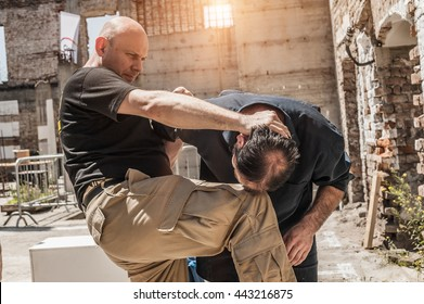 In a street fight one man strikes the other with knee to the head