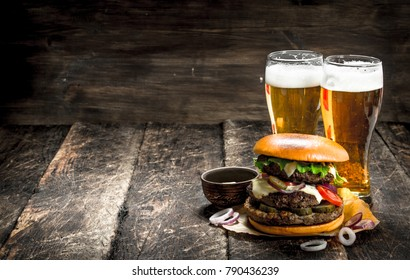Street food. A big burger with glasses of light beer. On a wooden background.