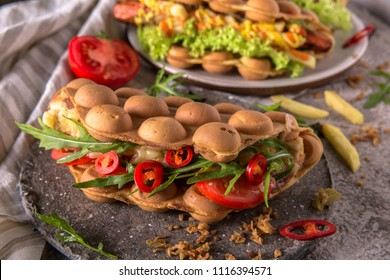 Street food. Big and tasty gourmet sandwich. Hong Kong style bubble waffles with sausage from minced meat, vegetables, cheese, fried egg, greens, French fries, sauces.  Nourishing, juicy, nutritious