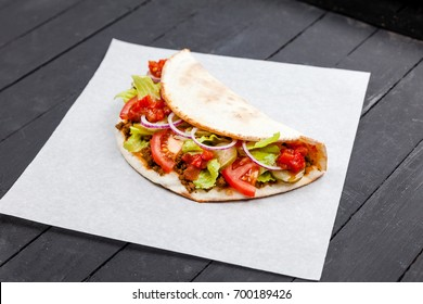Street food calzone, stromboli wrapped in paper on a black background