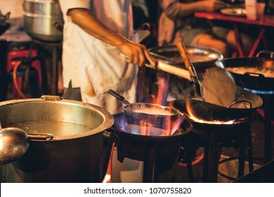 Street food chef cooking meat and fish in a pan with fire and flames under it. Chinatown, Bangkok, Thailand