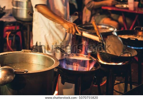 Le chef cuisinier de la rue cuisine de la viande et du poisson dans une casserole avec feu et flammes sous celle-ci. Chinatown, Bangkok, Thaïlande