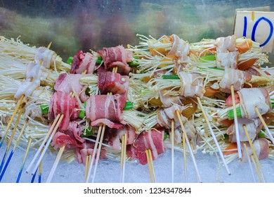Street food counter, mushrooms barbecue, mushroom roll with bacon, enoki bundles with meat. Traditional Chinese meal. Food Street Jalan Alor - in Kuala Lumpur, Malaysia.
