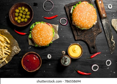 Street food. Fresh burgers with beef and vegetables. On the black chalkboard.