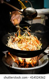 street food. fried noodles in a wok with chicken and shrimp on the open fire.Flat Lay, Chinese style