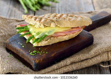 Street food: Hot Panini with ham and green asparagus topped with grated cheese served on a wooden background