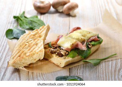 Street food: Hot Panini with Spanish Serrano ham and young spinach leaves topped with grated cheese served on a wooden background