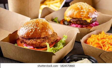 Street food. Meat cutlet burgers are in paper boxes. Food delivery. - Shutterstock ID 1824570860