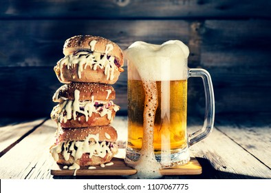 Street food. A mug of light beer and a huge burger. Appetizing homemade burger with beef patty in pub. closeup, rustic style