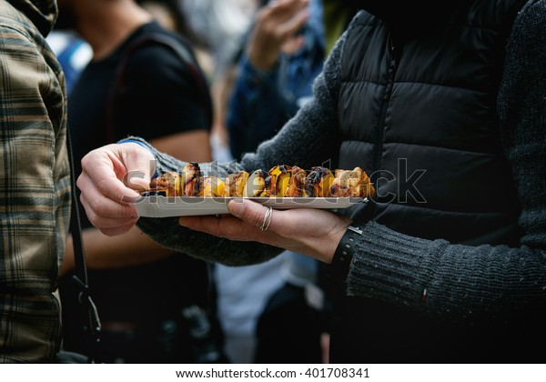 Street food at Prague market. Grilled chicken with vegetables on paper plate in hands.
